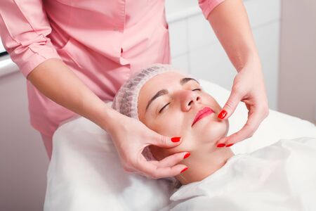 Young woman getting spa treatment at beauty salon. Spa therapy. Face Massage. Facial treatment. Skin and body care. Stock Photo