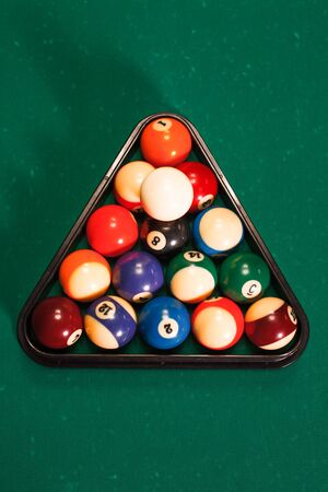 Balls in a pool triangle on the table. Green cloth Stock Photo