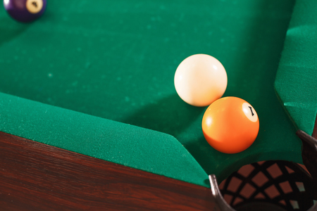 snooker: Above view on two billiard balls opposite to a pocket. Angle of the billiard table.