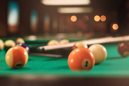 Billiard balls near by cue on the pool table. Blurred background. Lifestyle.
