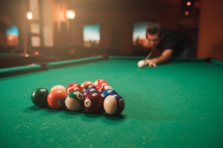 Player breaks a pyramid in billiards. Nightlife. Billiard room on the background.