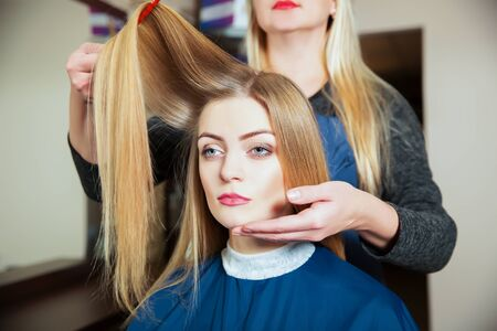 Professional hairdresser making hairstyle with hairbrush in hand to young female in hairdressing salon Stock Photo