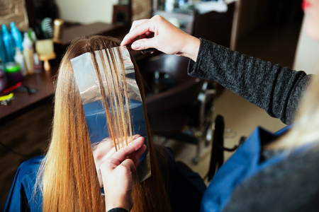 haircutter: Professional woman hairdresser uses foil for highlighting at beauty salon. Stock Photo