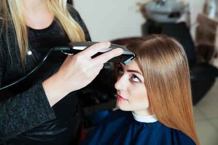 haircutting: Young female afraid shearing a zero machine for hair. Hair cute.