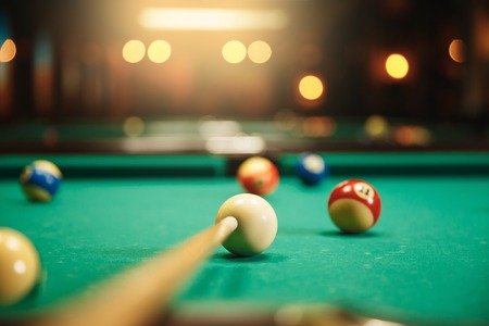 snooker room: Preparing to break spheres into the pool pocket. Green cloth. Blur background.
