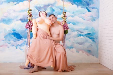 고무 섹스 인형 agaist 추상 수채화 배경으로 나무 벤치에 스윙 바지에 애정 남자.
