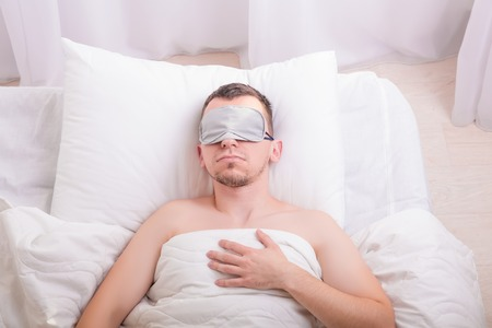 sleep mask: Sleeping young man in sleep mask on bed with big pillow. Comfort sleeping concept. Insomnia problem solution. Stock Photo