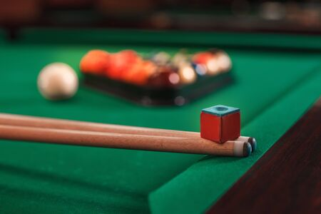 cues: Cues and chalk on a pool table. Billiard balls in triangle on the background.