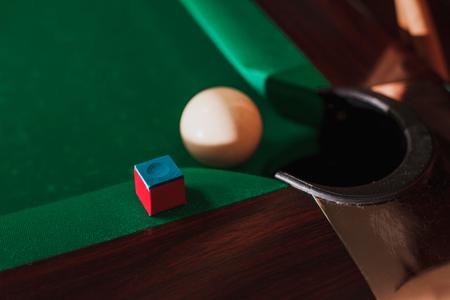 bola de billar: White pool ball opposite to a pocket.