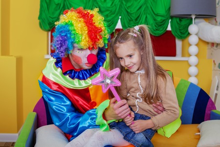 funny costume: Little girl playing with cheerful clown in funny costume. Friendship concept