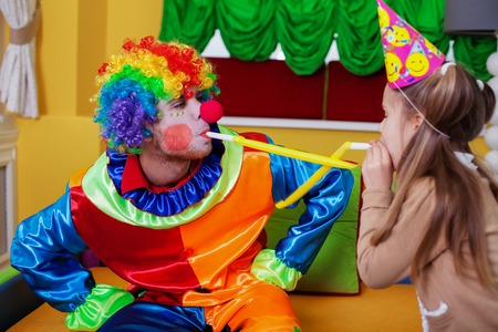 Happy clown and little girl plays with tube on birthday party. Stock Photo