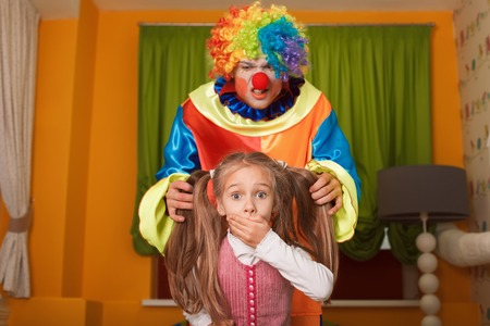 scared girl: Little girl was frightened of the clown who has crept behind. Kindergarten with colorful couch on the background.