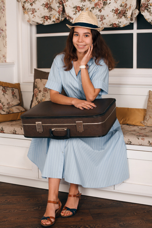 get ready: Young smiling woman with luggage sitting on sofa and get ready to travell. Journey concept.