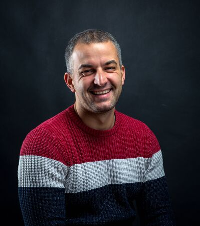 Portrait of smiling man in pullover isolated on black background. Brutal unshaven handsome man in professional studio.