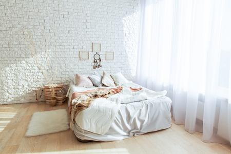 Chambre blanche minimaliste avec grand lit et mur de briques. Tout en couleurs blanches. Concept intérieur de chambre à coucher.