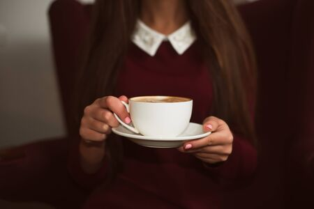 raspberry dress: Closeup female hands holding a cup of coffee on saucer.