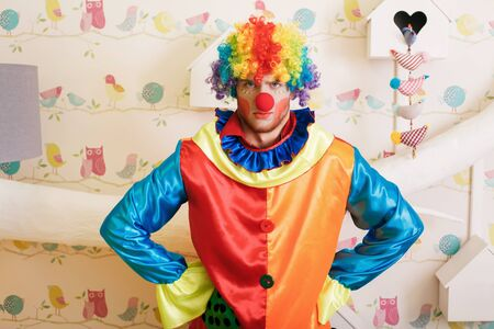 funny costume: Serious clown in funny costume standing in the playroom. Decorative birds and nesting box on the background. Stock Photo