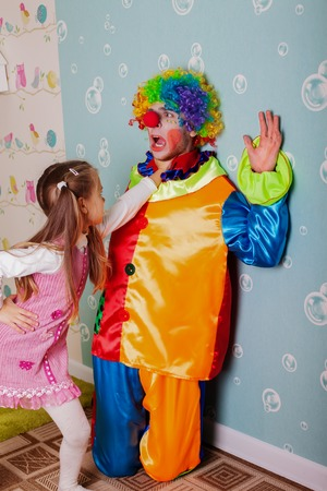 cruel: Cruel girl playing with scared clown at her birthday party Stock Photo