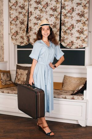 Young female traveler in white hat standing in the room with luggage.