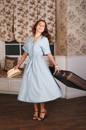 divan: Mujer sonriente que sostiene la maleta y el sombrero blanco en sus manos. Diván y una ventana con cortinas en el fondo. Estilo retro.