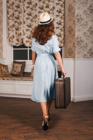 vintage travel: Young female standing in the room with suitcase. Vintage travel waiting concept.