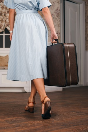 Female hands with wrist watch hold a suitcase. Young woman goes on a journey.