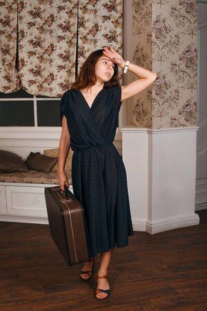 divan: Mujer sonriente que sostiene la maleta y el sombrero blanco en sus manos. Diván y una ventana con cortinas en el fondo
