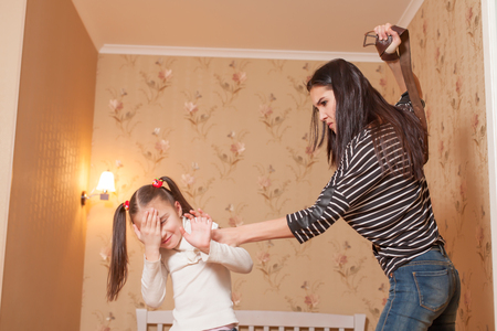 strict: Strict mother hit her little daughter with belt.
