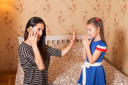 guardar silencio: Madre pide a la hija a mantenerse en silencio hasta ahora ella habla por teléfono Foto de archivo