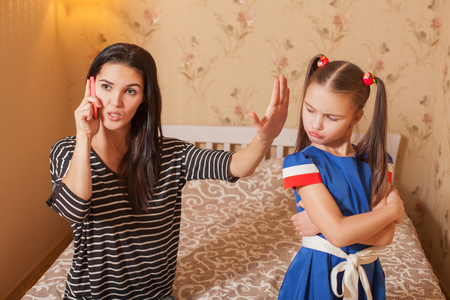 Mother asks the daughter to be silent till she speaks by phone Stock Photo
