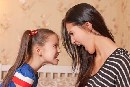 若い母親と彼女の小さな娘は、お互いにひどい顔をします。