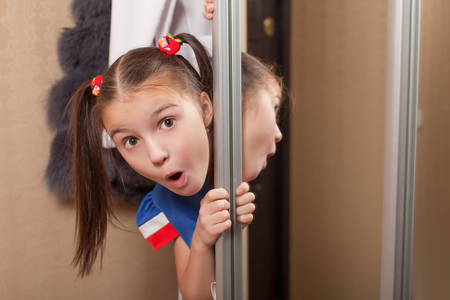 'hide out': Little girl looks out of the closet. Hide and seek theme. Stock Photo