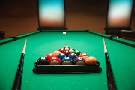 cues: Two cues and pyramid on a green billiard table. Pool theme.