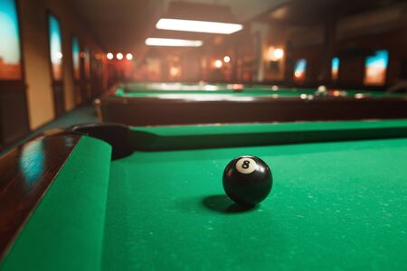 snooker rooms: Sphere number 8 opposite to a billiard pocket. Billiard room on the background.