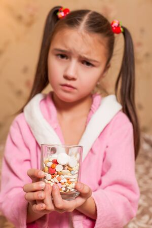 Sad little girl with glass full of tablets and pills in her hands. Stock Photo