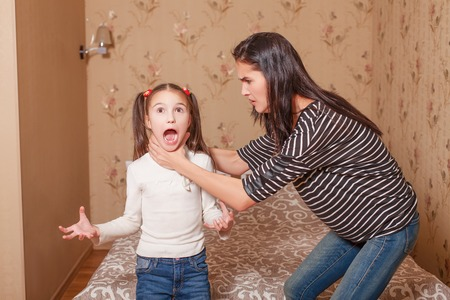 Angry mother trying to strangle her little daughter.
