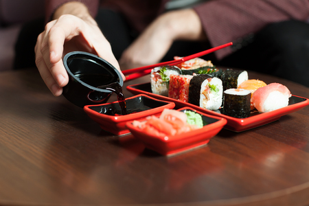 Male hands pours sauce in a plate. Sushi set on wooden table.