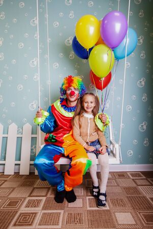 Happy little girl with the clown shake on a swing. Clown hold air balloons in his hands. Stock Photo