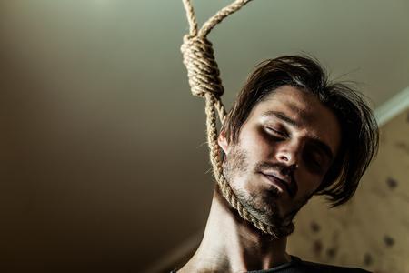 Suicide concept, depressed man with a noose around his neck.