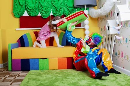 niñas pequeñas: Niña feliz que late payaso con una almohada grande. Sala de juegos con sofá de colores en el fondo.