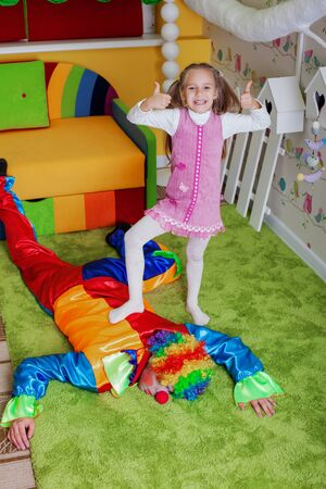 Young girl has won a game against the clown. Birthday party entertainment concept.