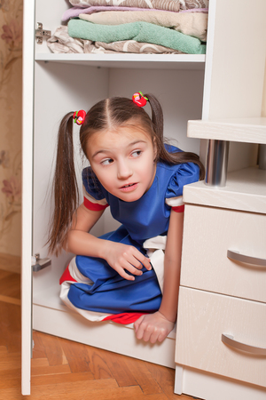 'hide out': Female child looks out of the closet. Hide and seek concept. Stock Photo