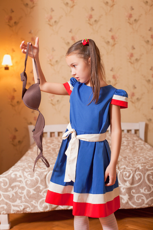 Surprised little girl holds a bra in hand. Bedroom on the background. Stock Photo