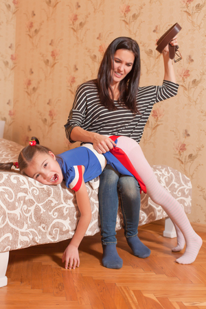 Angry mother beat her little daughter with belt. Strict education concept. Stockfoto
