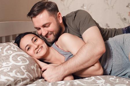 pareja abrazada: Abrazar la joven pareja acostada en la cama.
