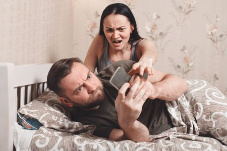 Wife irritate while husband using phone in bed. Couple quarrel concept.