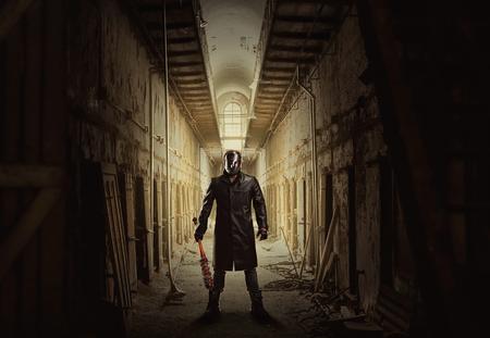 Moordenaar met bloedige vleermuis in verlaten gebouw.