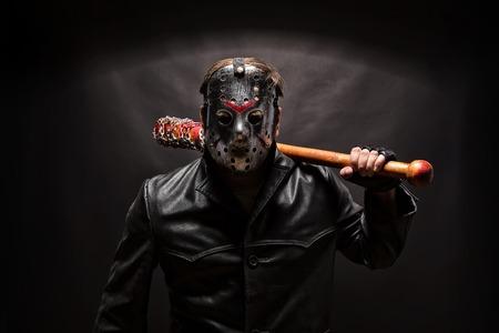 Psycho killer in hockey mask on black background.