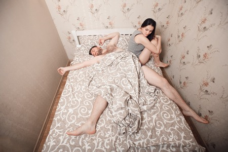 Man has occupied all bed, woman sit on the edge.