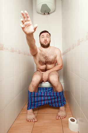 Scared man in toilet. Stock Photo - 69803333